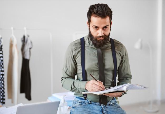 Vista frontal del guapo diseñador de moda masculino en atelier con papeles