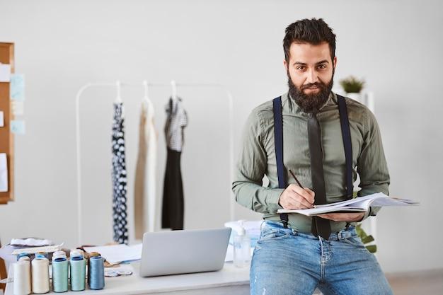 Vista frontal del guapo diseñador de moda masculino en atelier