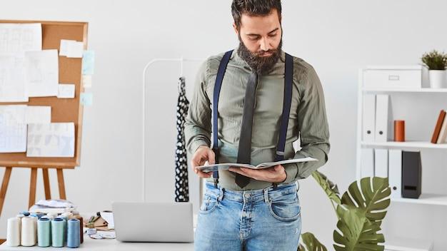 Vista frontal del guapo diseñador de moda masculino barbudo en atelier