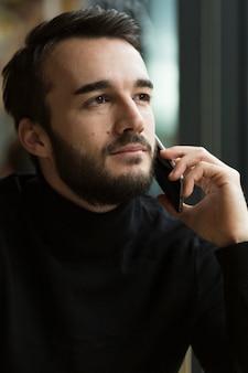 Vista frontal guapo hombre hablando por teléfono