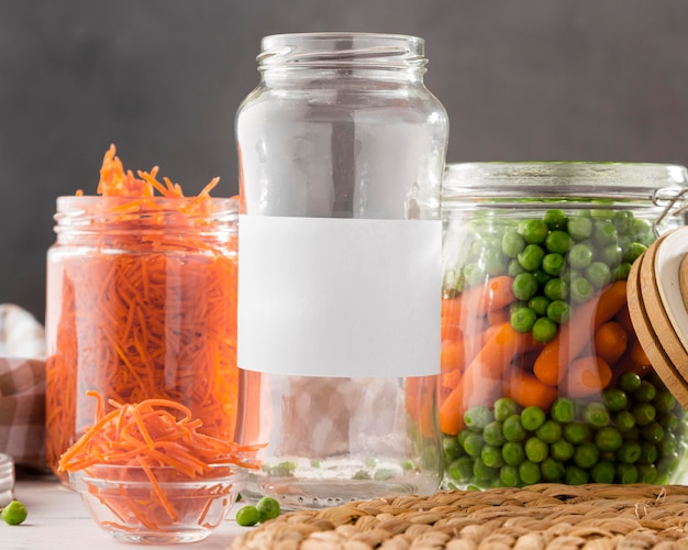 Vista frontal de guisantes en escabeche y zanahorias pequeñas en frascos de vidrio transparente