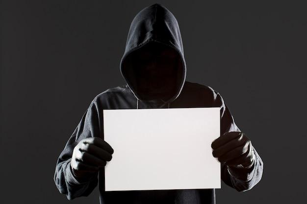 Vista frontal del hacker masculino con guantes con papel en blanco