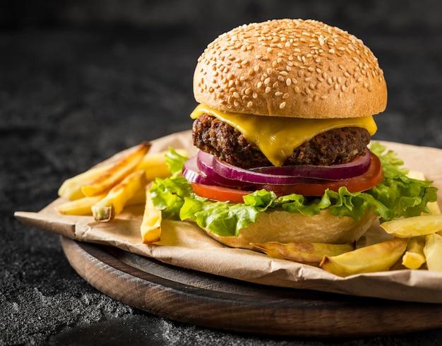 Vista frontal hamburguesa fresca y papas fritas en placa