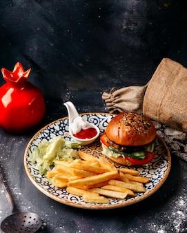 Vista frontal hamburguesa junto con papas fritas en la superficie gris