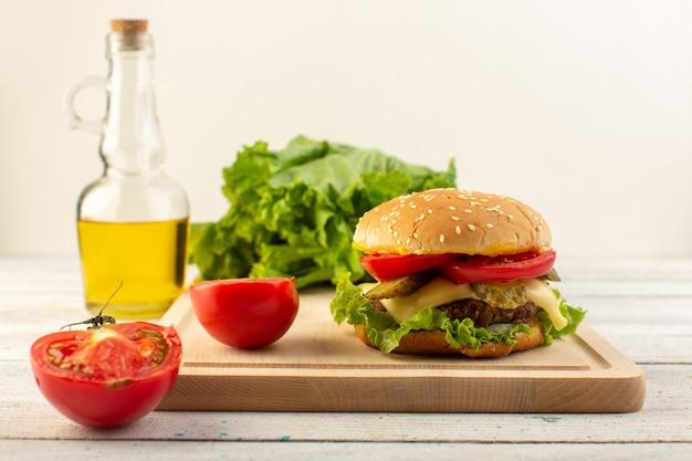 Vista frontal de una hamburguesa de pollo con queso y ensalada verde y aceite de oliva en el escritorio de madera y sándwich de comida rápida.