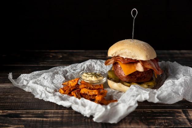 Vista frontal hamburguesa con queso y batatas fritas con salsa