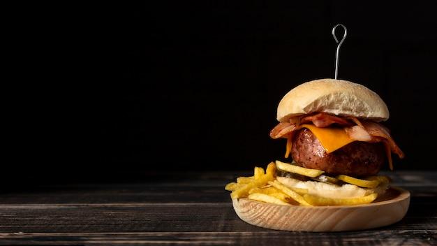 Vista frontal hamburguesa con queso y papas fritas en bandeja de madera con espacio de copia