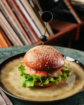 Una vista frontal hamburguesa sabrosa con ensalada verde y otros ingredientes dentro del plato redondo en la superficie oscura