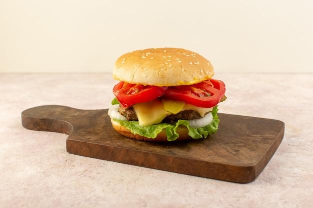 Una vista frontal de hamburguesas de carne con verduras, queso y ensalada verde en la mesa de madera