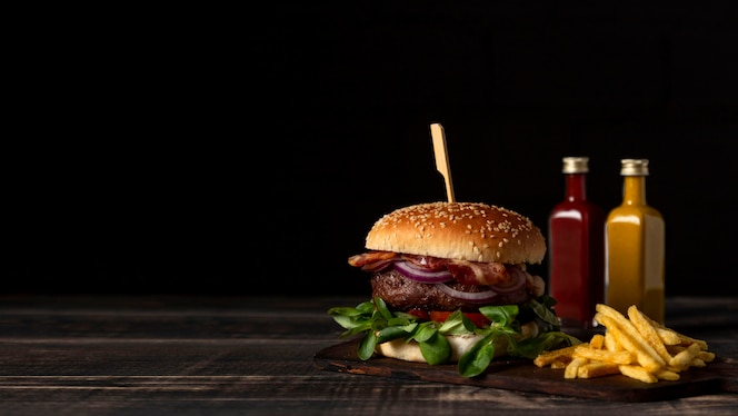 Vista frontal de hamburguesas y papas fritas en la mesa con salsas y espacio de copia