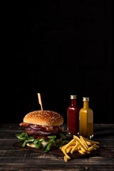 Vista frontal de hamburguesas y papas fritas con salsas en la mesa y espacio de copia