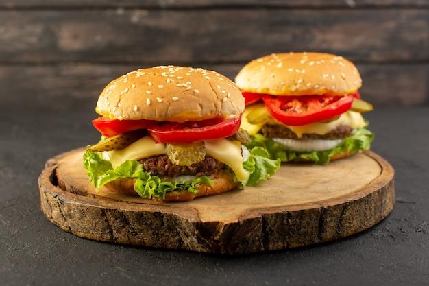 Una vista frontal de hamburguesas de pollo con queso y ensalada verde en el escritorio de madera y sándwich de comida rápida.