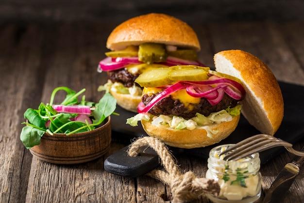 Vista frontal de hamburguesas de ternera con pepinillos y cebollas rojas en la tabla de cortar