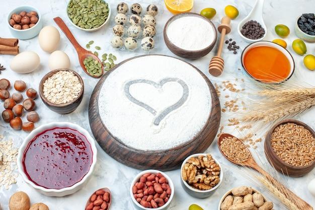 Vista frontal de harina en forma de corazón con gelatina huevos diferentes nueces y semillas sobre fondo blanco masa pastel de azúcar foto nuez galleta de color dulce