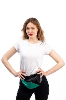 Una vista frontal hembra joven en camiseta blanca y jeans negros con bolsita en el blanco