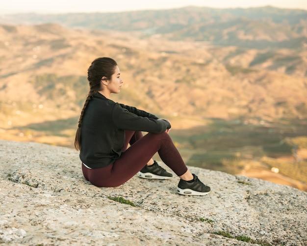 Vista frontal hembra joven sentada en la cima de la montaña