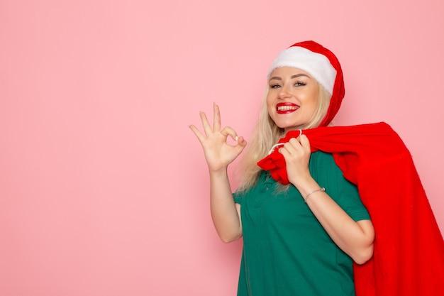 Vista frontal de las hembras jóvenes que llevan bolsa roja con regalos en la pared rosa modelo vacaciones navidad año nuevo color foto santa