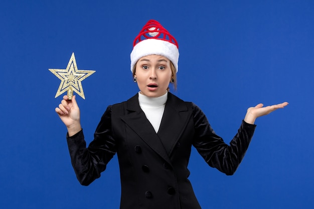 Vista frontal de las hembras jóvenes que sostienen el juguete en forma de estrella en la pared azul vacaciones mujer año nuevo