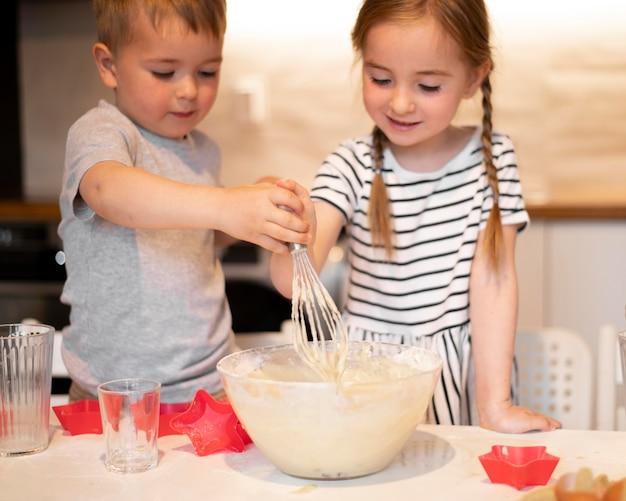 Vista frontal de hermanos cocinando en casa