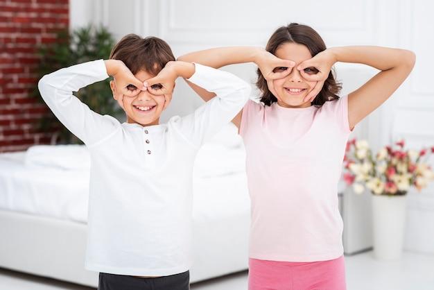 Vista frontal hermanos juguetones divirtiéndose en casa