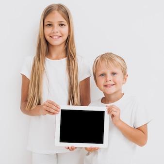 Vista frontal hermanos sosteniendo una maqueta de tableta