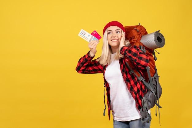 Vista frontal hermosa chica rubia con su mochila con tarjeta y boleto de viaje