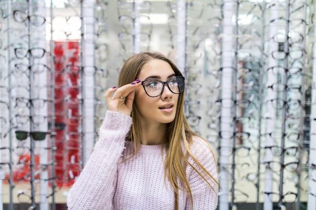 Vista frontal de la hermosa chica en suéter blanco pruebe gafas en tienda profesional en