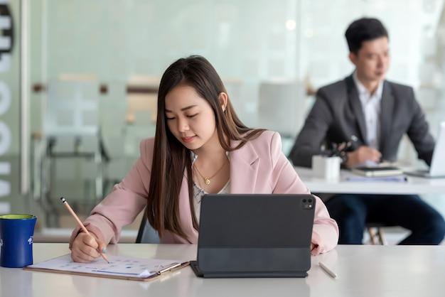 Vista frontal de una hermosa empresaria asiática sosteniendo un lápiz con documentos una tableta colocada en la oficina.