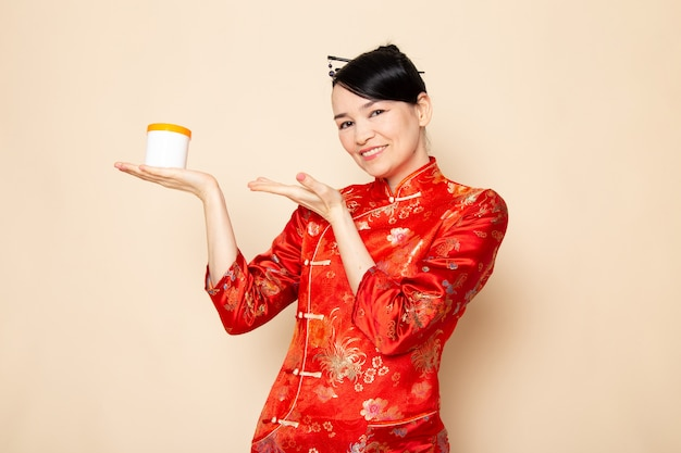 Una vista frontal hermosa geisha japonesa en el tradicional vestido rojo japonés con palos para el cabello posando sosteniendo la crema puede sonreír en la ceremonia de fondo crema japón