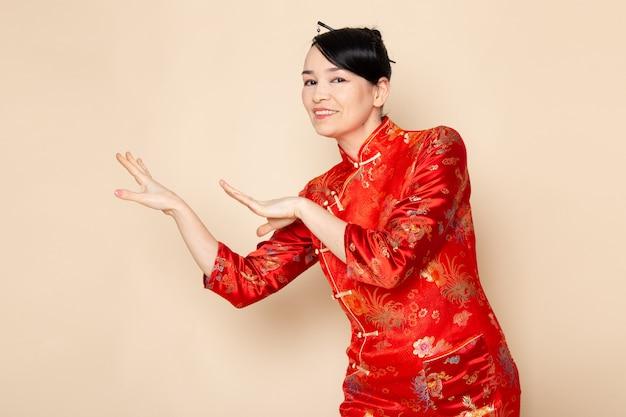 Una vista frontal hermosa geisha japonesa en el tradicional vestido rojo japonés con palos para el pelo posando de pie feliz en la ceremonia de fondo crema entretenido este de japón