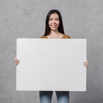 Vista frontal hermosa joven con un cartel