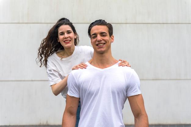 Vista frontal de la hermosa joven pareja abrazándose, mirando a la cámara y sonriendo mientras está de pie al aire libre