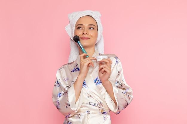 Una vista frontal hermosa jovencita en bata de baño haciendo maquillaje con sonrisa