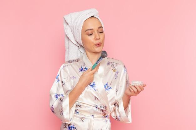Una vista frontal hermosa jovencita en bata de baño haciendo maquillaje