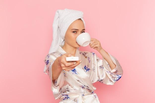 Una vista frontal hermosa jovencita en bata de baño tomando café y apagando el aire acondicionado