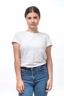 Una vista frontal hermosa jovencita en camiseta blanca y jeans azul posando