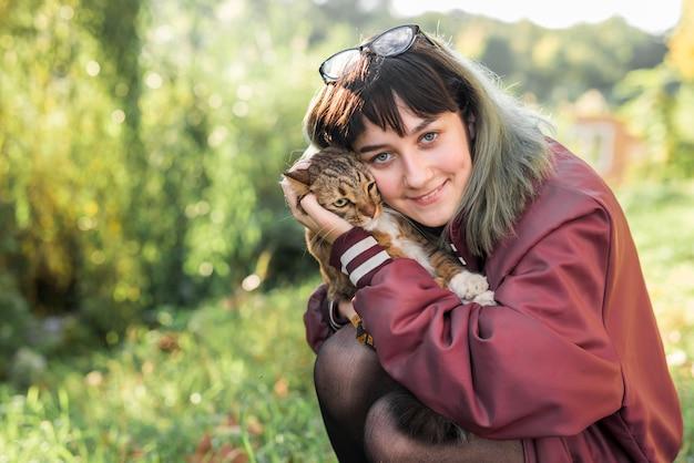 Vista frontal de la hermosa mujer abrazando a su gato atigrado en el parque