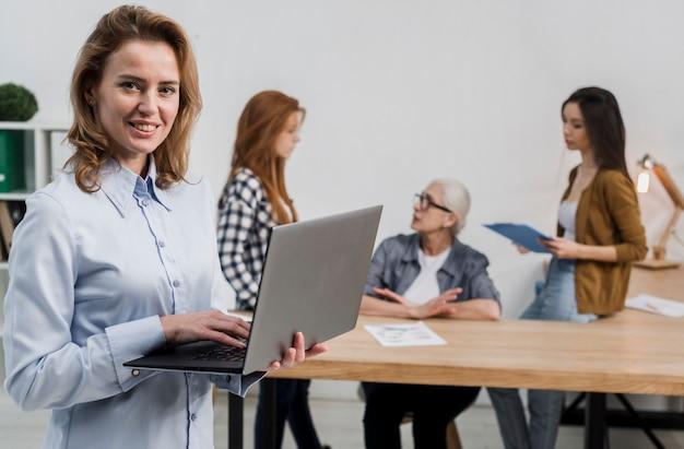 Vista frontal hermosa mujer adulta sosteniendo una laptop