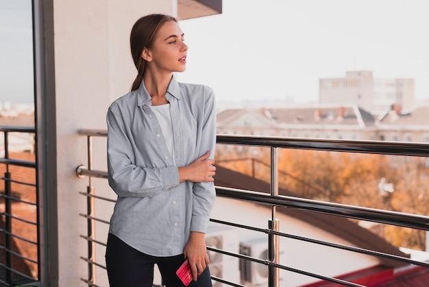 Vista frontal hermosa mujer en el balcón