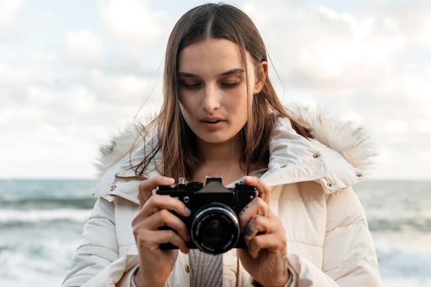 Vista frontal de la hermosa mujer con cámara en la playa