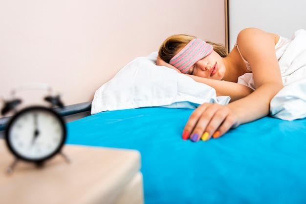 Vista frontal hermosa mujer durmiendo en la cama