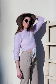 Vista frontal de la hermosa mujer joven de moda con gafas de sol y sombrero de pie en la calle mientras posa en un día soleado