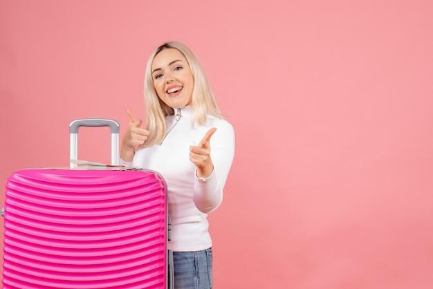 Vista frontal hermosa mujer con maleta rosa apuntando al frente
