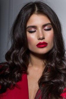 Vista frontal de la hermosa mujer con maquillaje y cabello rizado