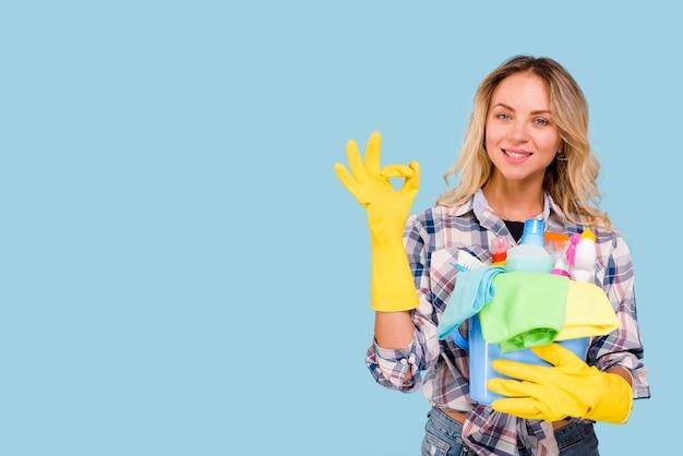 Vista frontal de la hermosa mujer mostrando signo bien mientras sostiene productos de limpieza en balde contra el fondo azul