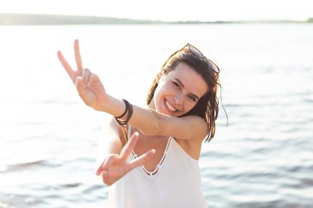 Vista frontal hermosa mujer mostrando el signo de la paz