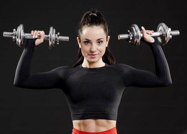 Vista frontal de hermosa mujer con pesas