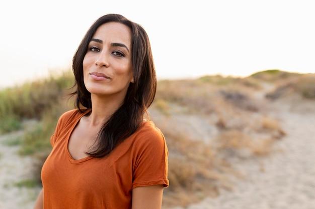 Vista frontal de hermosa mujer posando junto a la playa
