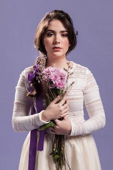 Vista frontal de la hermosa mujer posando con ramo de flores