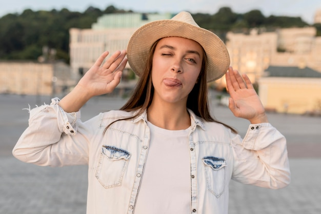 Vista frontal de la hermosa mujer posando tonta con sombrero mientras viaja